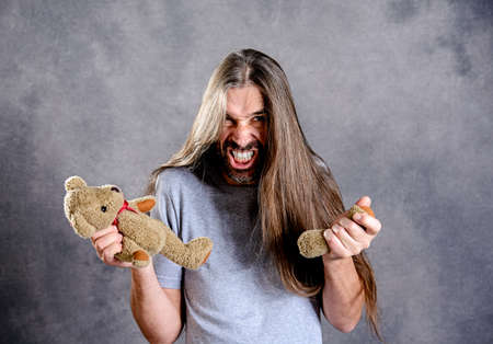 young long haired man with broken teddy bear looking bad