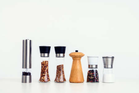different spice mills with salt,pepper and other herbs in front of white background