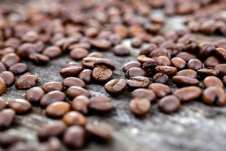 a lot of brown roasted coffee beans on wooden ground
