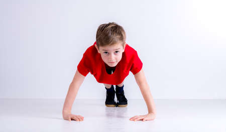 boy in red shirt doing push- ups in front of white background Stock Photo