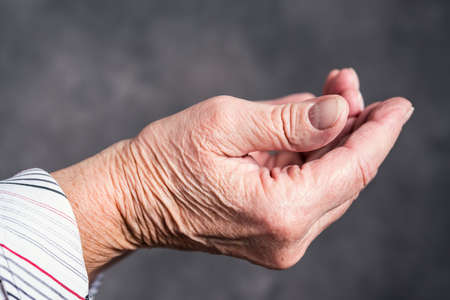 open hands of  elderly woman in front of dark background Banco de Imagens