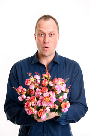 young man with bunch of flowers in front of white background