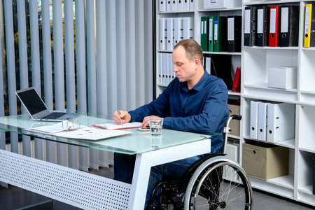 Disabled businessman in wheelchair working in the office Banque d'images
