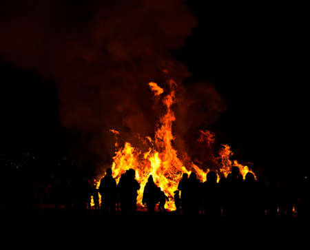 Silhouettes of people in front of big easter fire Stock Photo