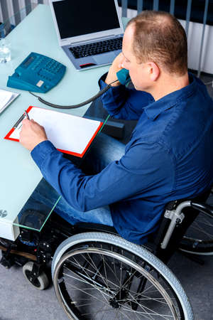 Disabled businessman in wheelchair working in the office Stock Photo