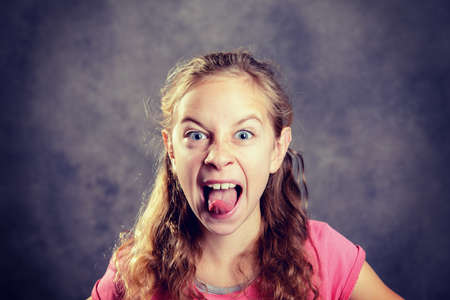 girl with blond hair and pink shirt making grimace