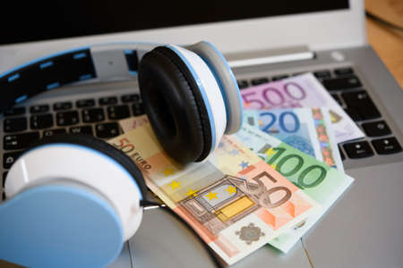 computer keyboard with headphones and euro bank notes