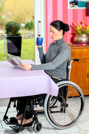 young disabled woman in wheelchair at home reading newspaper and drinking coffee