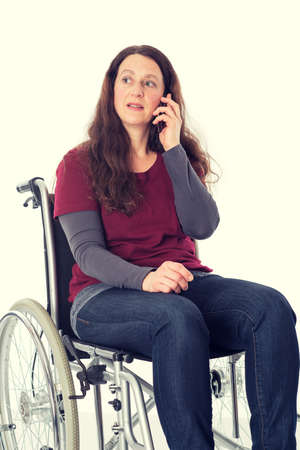 young woman in wheelchair calling with cellphone Stock Photo