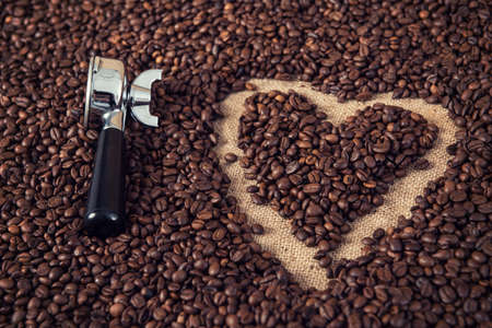 heart in a lot of coffee beans with heart with portafilter Stock Photo