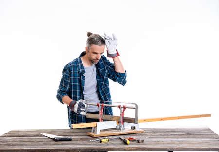 Arbeiter im blauen karierten Hemd, das Holz sägt