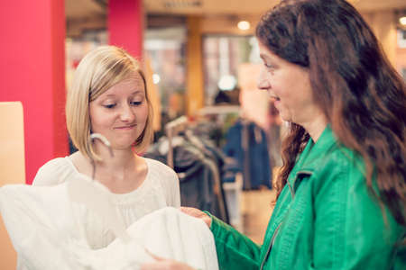 two women in the clothes shop looking for outfit