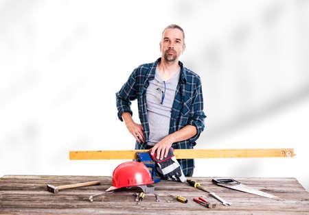 Arbeiter im blauen karierten Hemd mit rotem Helm auf Werkbank