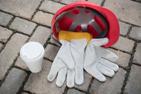 red helmet,coffee mug and work gloves on stones