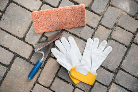 trowel, sponge board and work gloves on stone ground