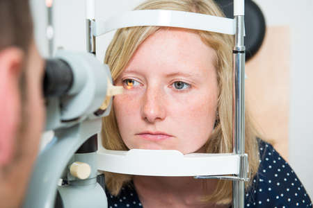ophthalmologist checking eyes of woman for new glasses