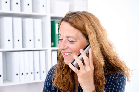 brown-haired  businesswoman calling in the office