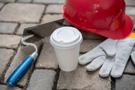 red helmet, trowel,coffee mug and work gloves on stones