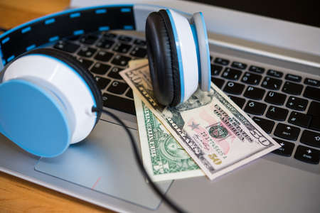 computer keyboard with headphones and dollar bank notes