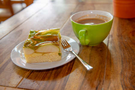 fruit cake with milk- coffee in a green cup Foto de archivo