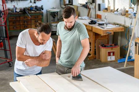two men in workwear in a carpenters workshop
