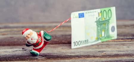 little Santa Claus pulling big euro banknote Stock Photo