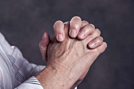 wrinkly hands of  elderly woman praying in front of dark background