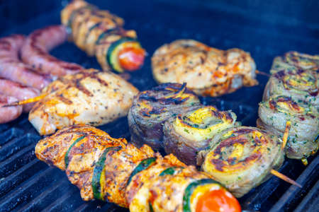 different meat and sausage on gas barbecue