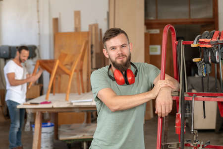 man in workwear in a carpenters workshop looking in to the camera