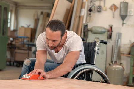 pracownik niepełnosprawny na wózku inwalidzkim w warsztacie stolarskim