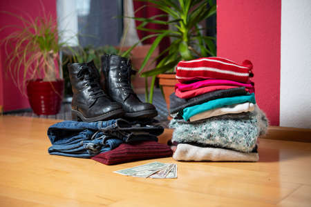 pile of second hand clothing and  shoes with money on floor in living room