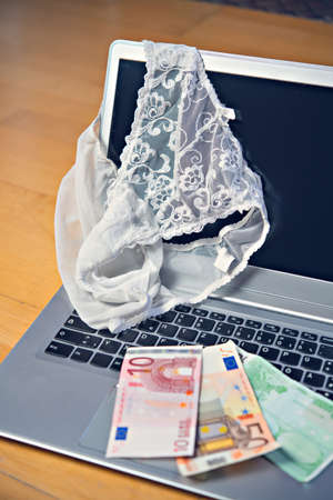 white woman panties with silver laptop- computer and money 스톡 콘텐츠