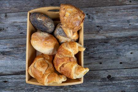 diversi panini freschi e croissant in cesto di legno in vista dall'alto