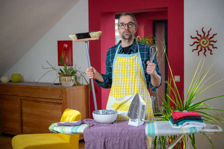 man with iron,broom, bowl and whisk in living room