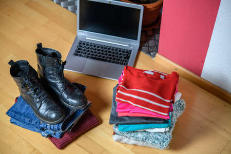 tas de vêtements et de chaussures d'occasion avec ordinateur sur le sol dans le salon