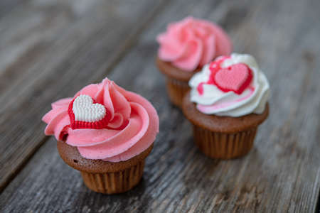 pink and white muffins on wooden ground with heart whipping cream Foto de archivo