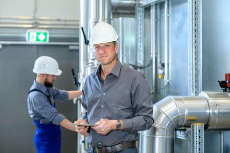 Chef mit Arbeiter im Hintergrund in seiner Fabrik