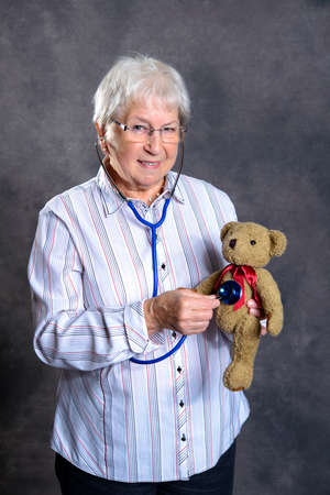 gray haired grandmother with stethoscope is puppet doctor for teddy bear