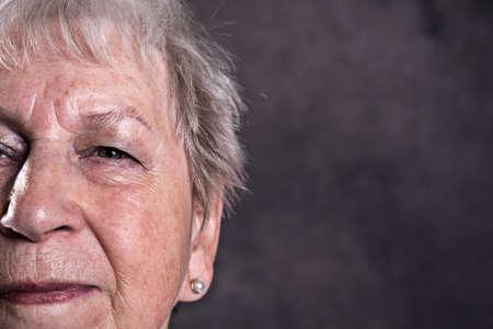 close up portrait of  elderly woman in front of dark background