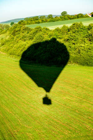 shadow of a hot- air balloon on green landscape from above Imagens
