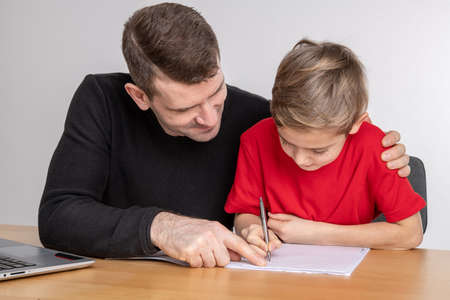 father helping his son with homework at table 版權商用圖片