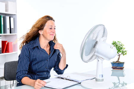business woman with ventilator at his desk in summerly hot office Stok Fotoğraf