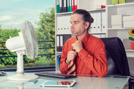 business man with ventilator at his desk in summerly hot office