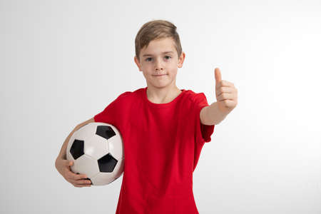 boy in red shirt with soccer ball and thumb up in front of white background