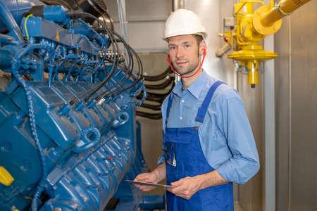 worker with helmet and clipboard working on big generator