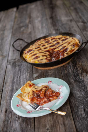 sweet pie in iron pan on wooden ground