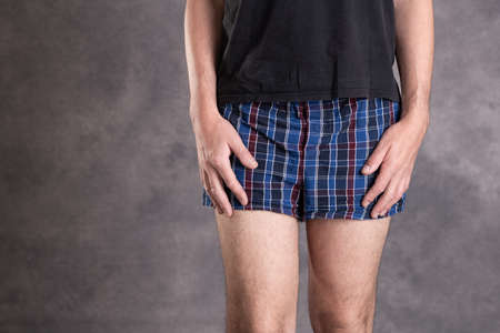 man in blue plaid boxer shorts in front of gray background