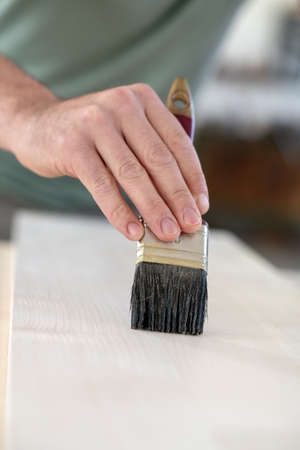 worker in a carpenter's workshop painting wood with brush