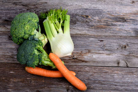 green broccoli, spring onions,fennel and carrots on wooden board