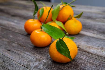mandarin orange with leaf on wooden ground